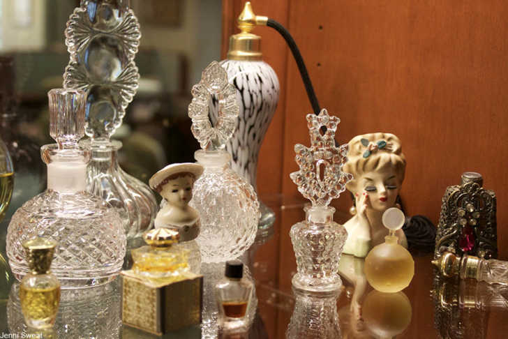 collection of lady head vases and vintage perfume bottles on mirrored surface