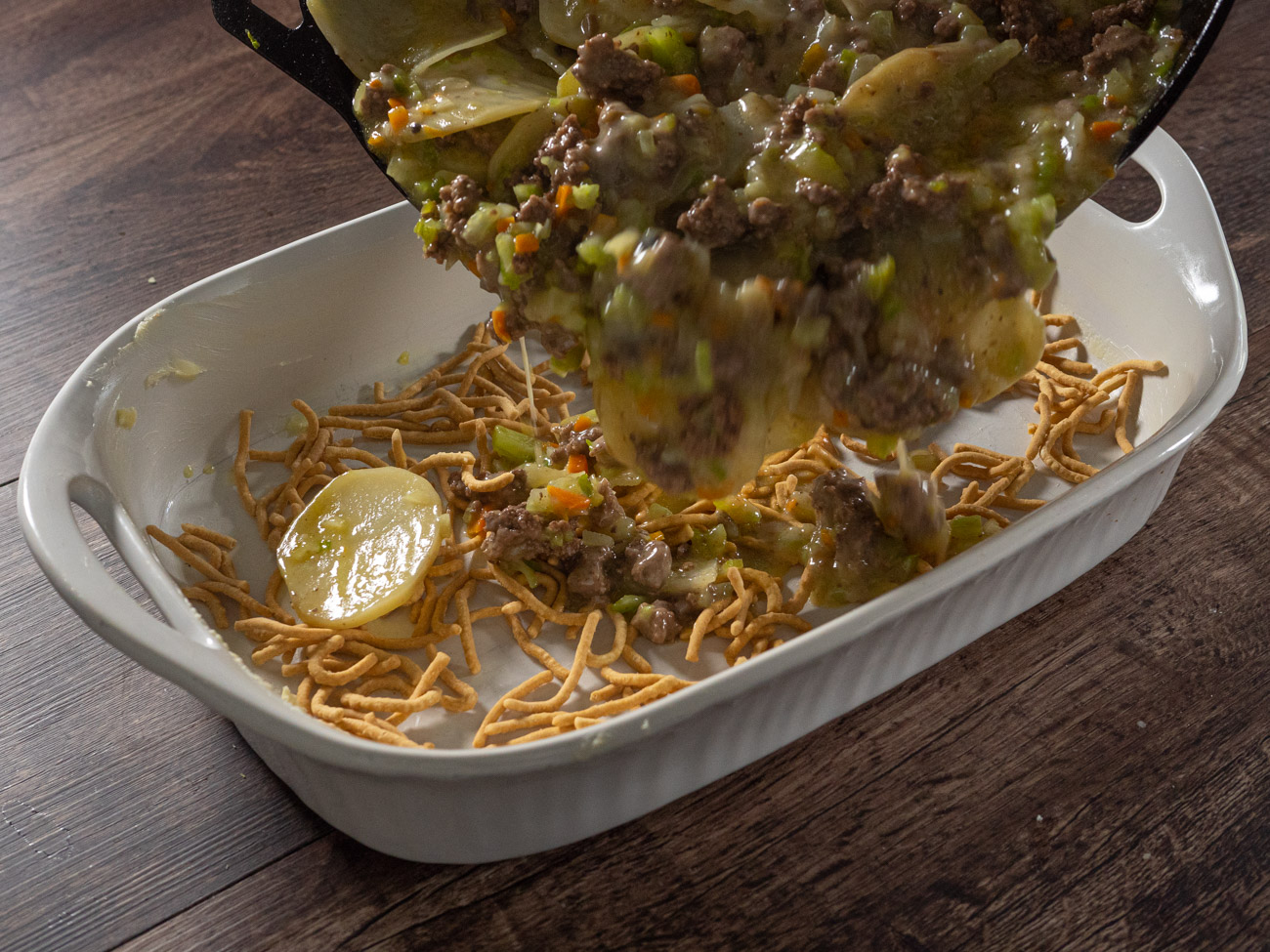Line casserole dish with half the chow mein noodles and spoon beef and vegetable mixture on top.