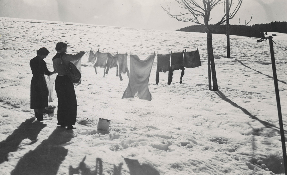 black and white photo of two women hanging out laundry in the snow