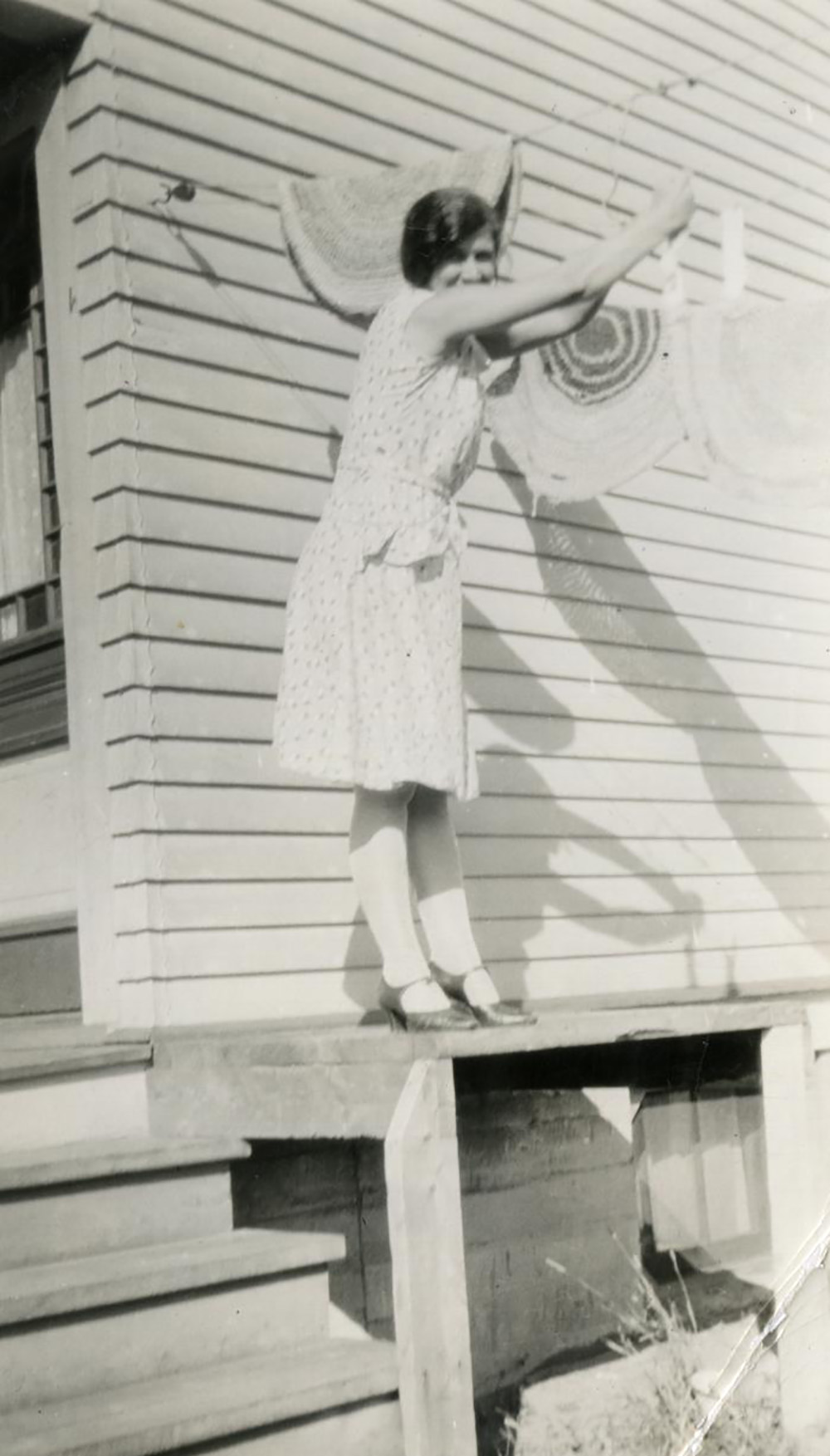 black and white photo of a 1940s woman hanging out laundry