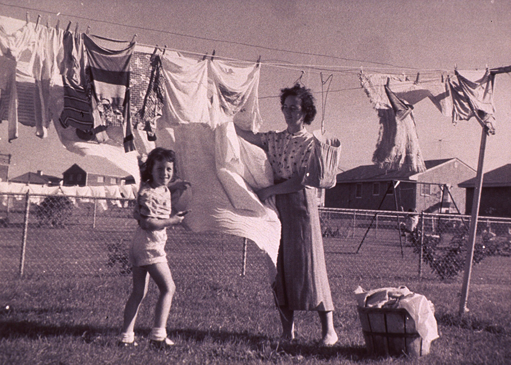 1950s mother and daughter hanging out clothes together