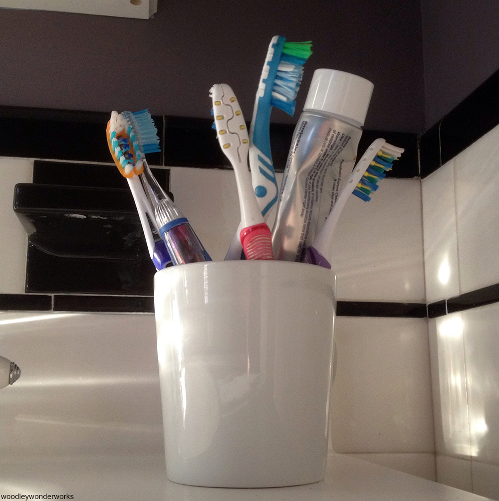 toothbrush holder filled with toothbrushes and toothpaste