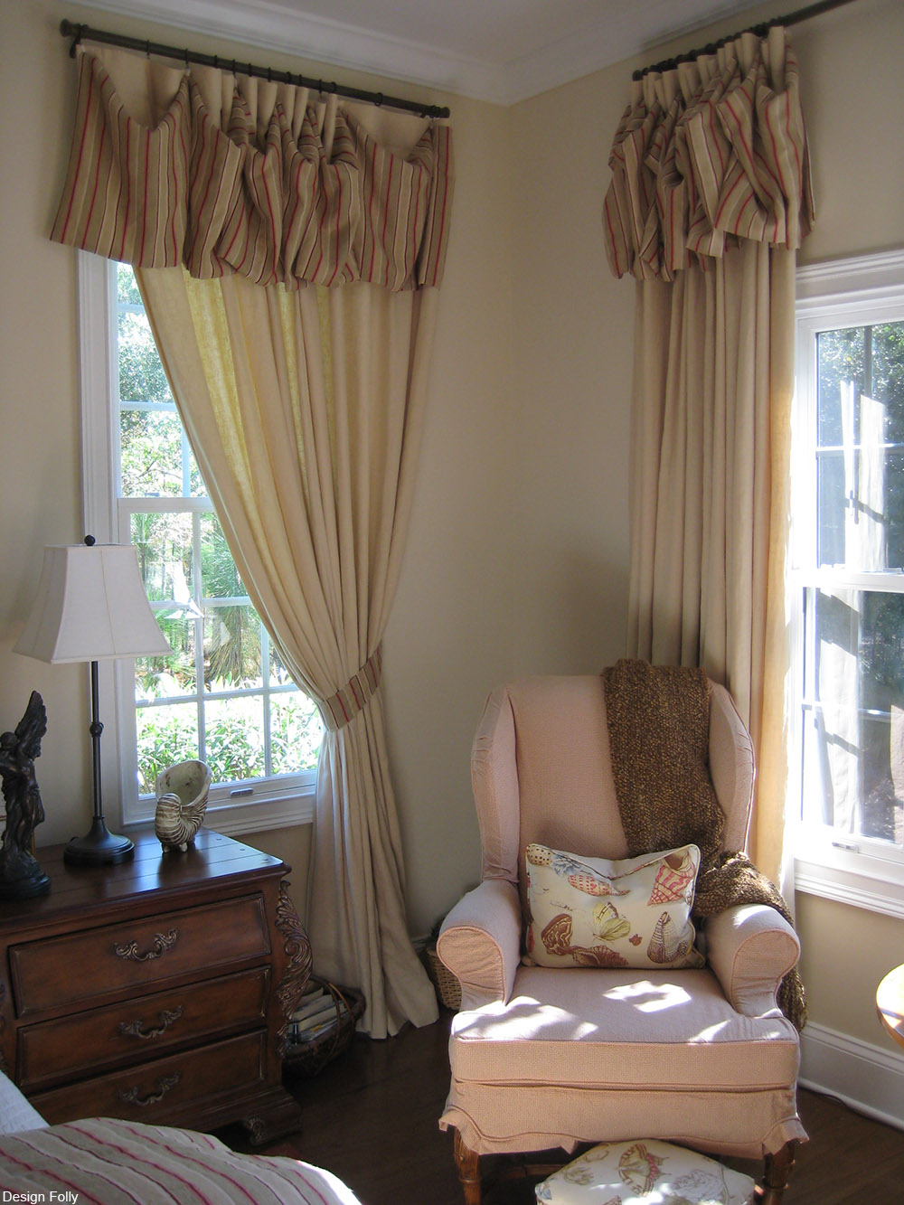 armchair by two windows with drapes