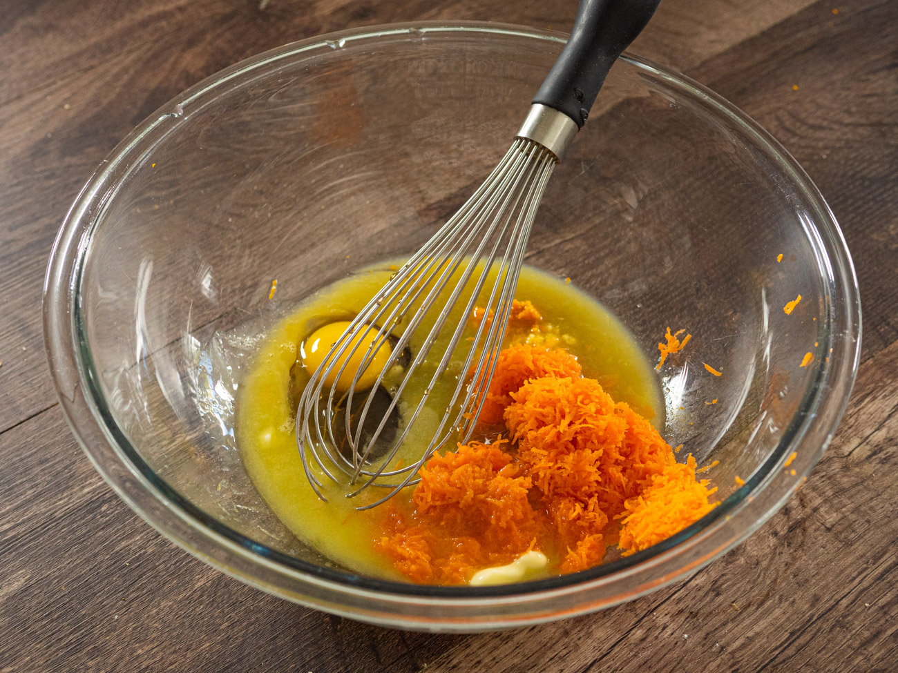 In a large bowl, combine the egg, orange zest, maple syrup, orange juice, melted butter, and fresh ginger until well blended. Fold in grated carrots.