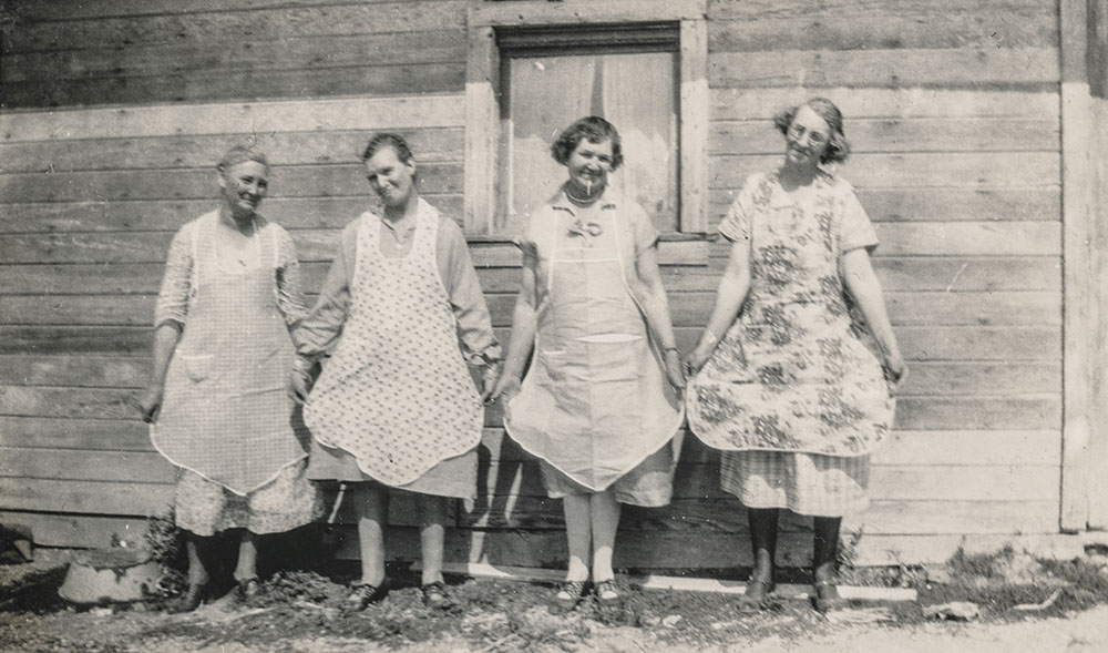 Women showing off their aprons, 1930s