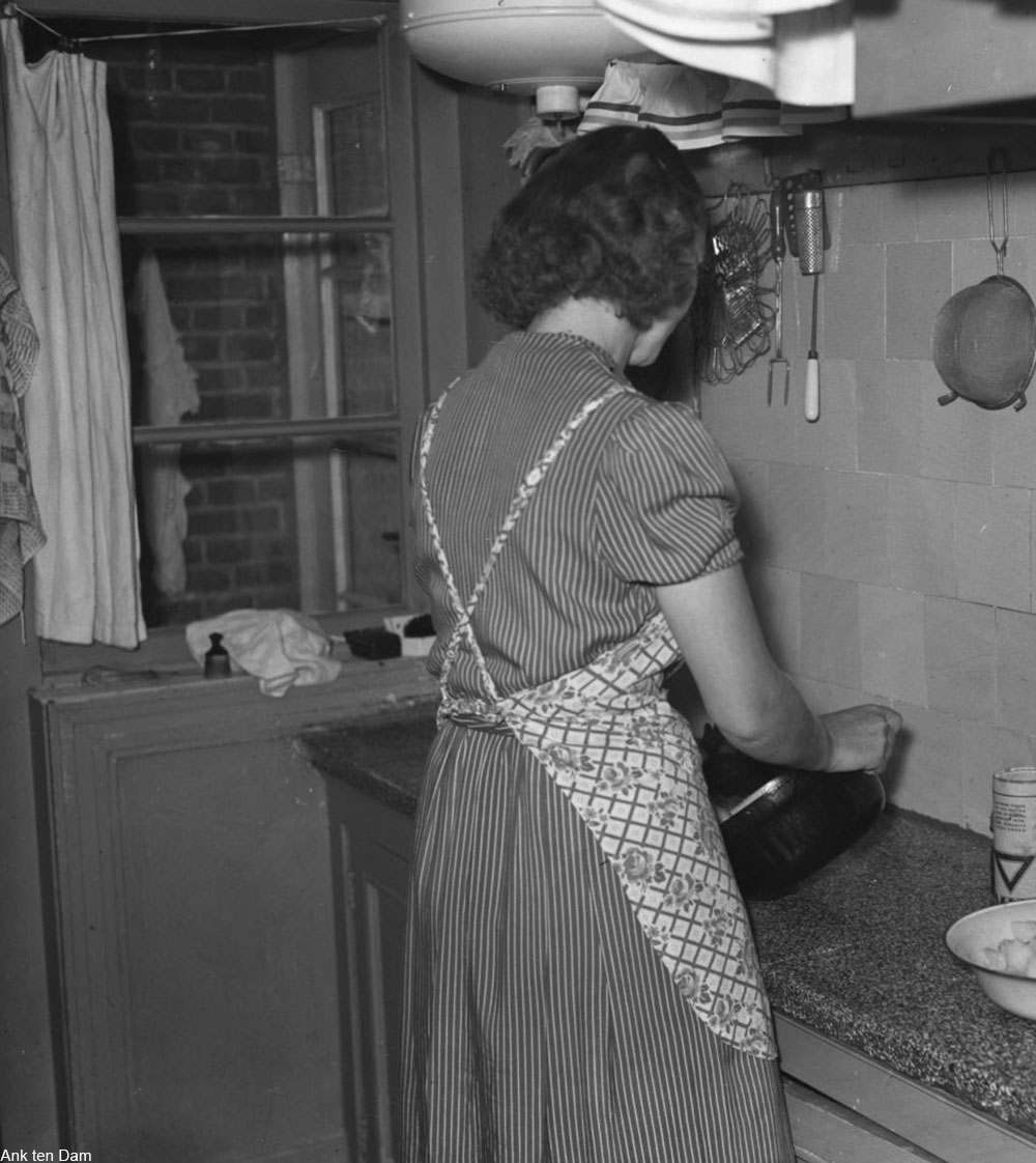 woman making food in a crossback apron, 1940s