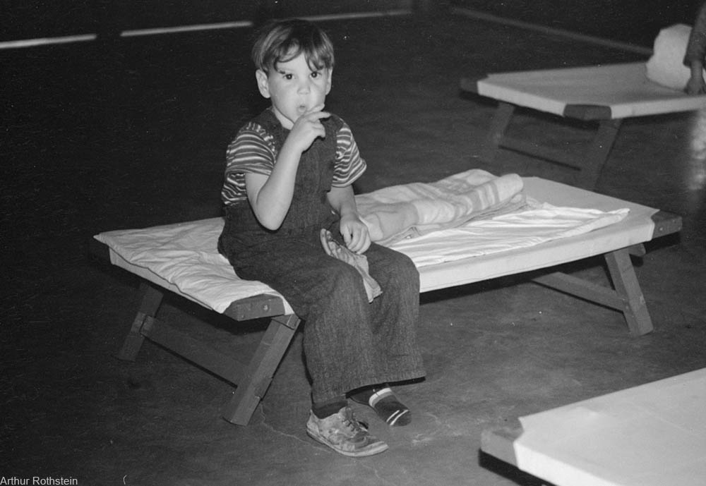 young boy on cot at school making funny face