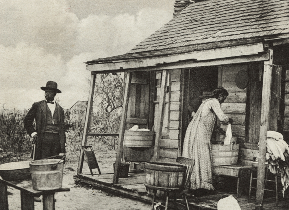 black and white photo of an American settler woman doing laundry