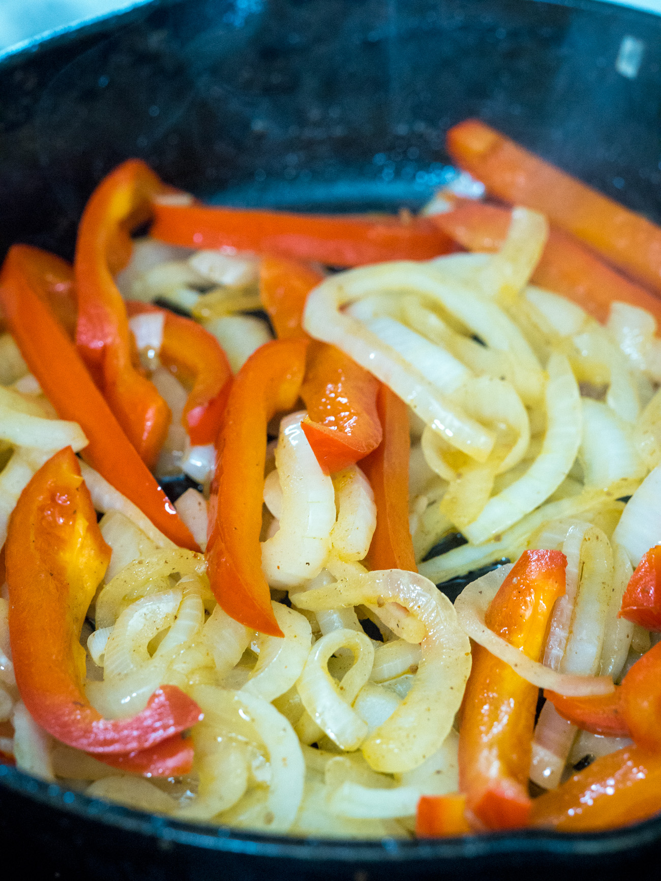 In the same skillet sauté bell peppers and half the onions. Set aside.
