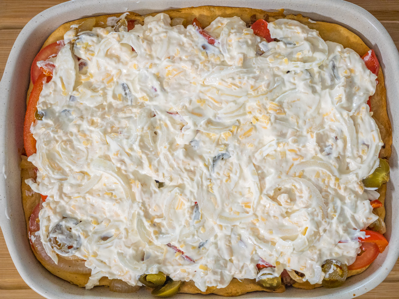Layer the beef on top of the biscuit crust, followed by the sliced tomatoes, and then the pepper and onion mixture, adding jalapeños on top of that. Add the sour cream mixture on top of the vegetables and top with remaining cheese.