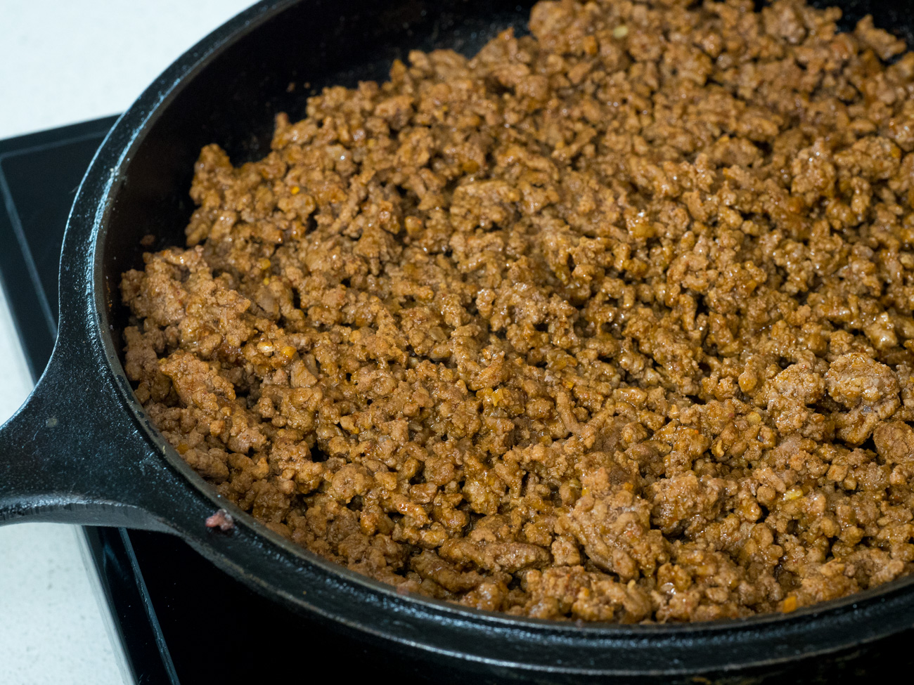 In a large skillet over medium heat, brown the ground beef and onions until beef is no longer pink. Drain any excess fat and season beef with taco seasoning. Add 1/4 cup water and simmer until water has reduced completely. Remove from heat and set aside.