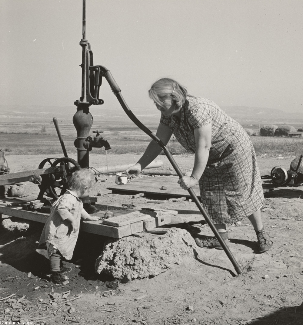 Mrs. Soper with youngest child at the well. Willow creek area, Malheur County, Oregon, 1939