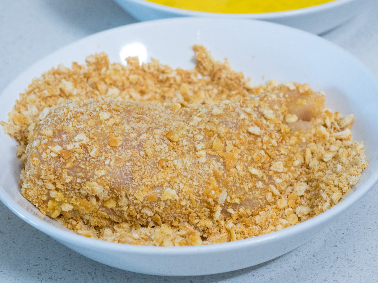 Dip chicken in beaten eggs, and then dredge in cracker crumbs, pressing mixture into the meat.