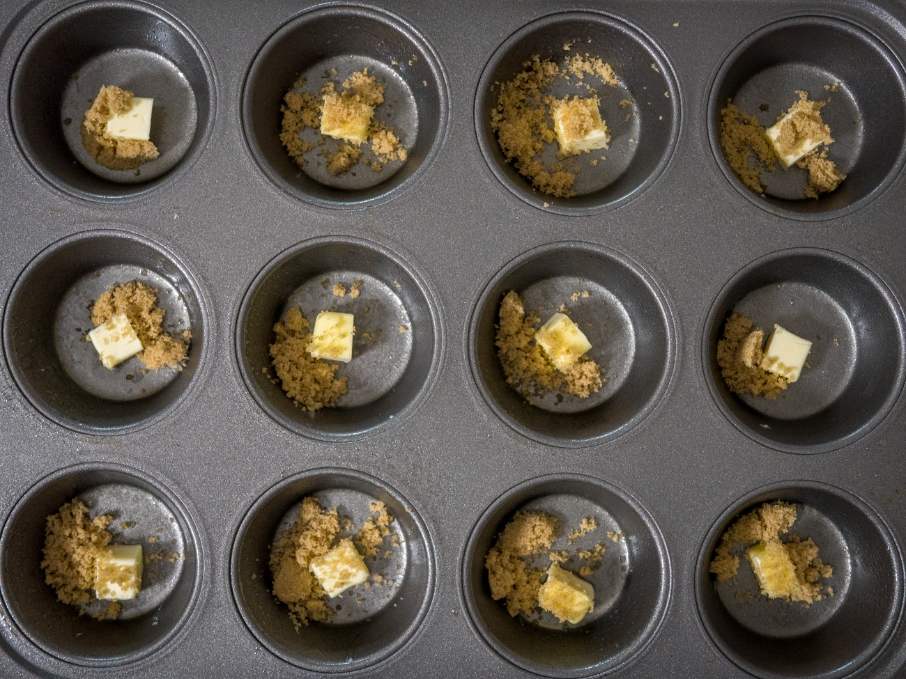 Prepare the muffin tin by dividing the 1 tablespoon of butter into 12 portions, placing one portion in each of the 12 cups of the cups. Sprinkle 1/2 teaspoon of brown sugar into each cup as well.