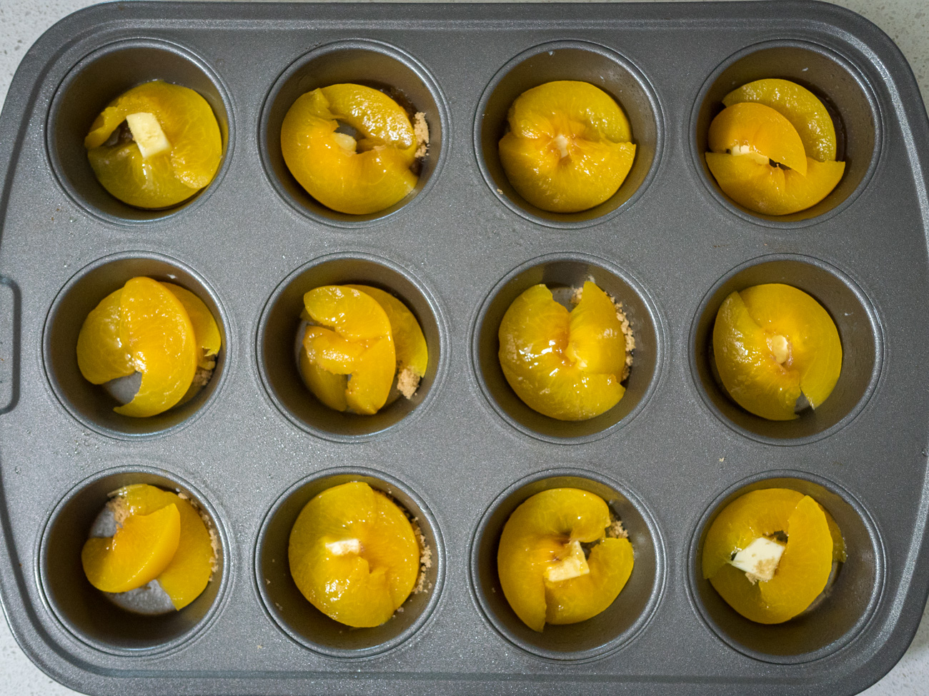 Slice 1-2 peaches into thin slices. Put about 3 slices into the bottom of each muffin cup.