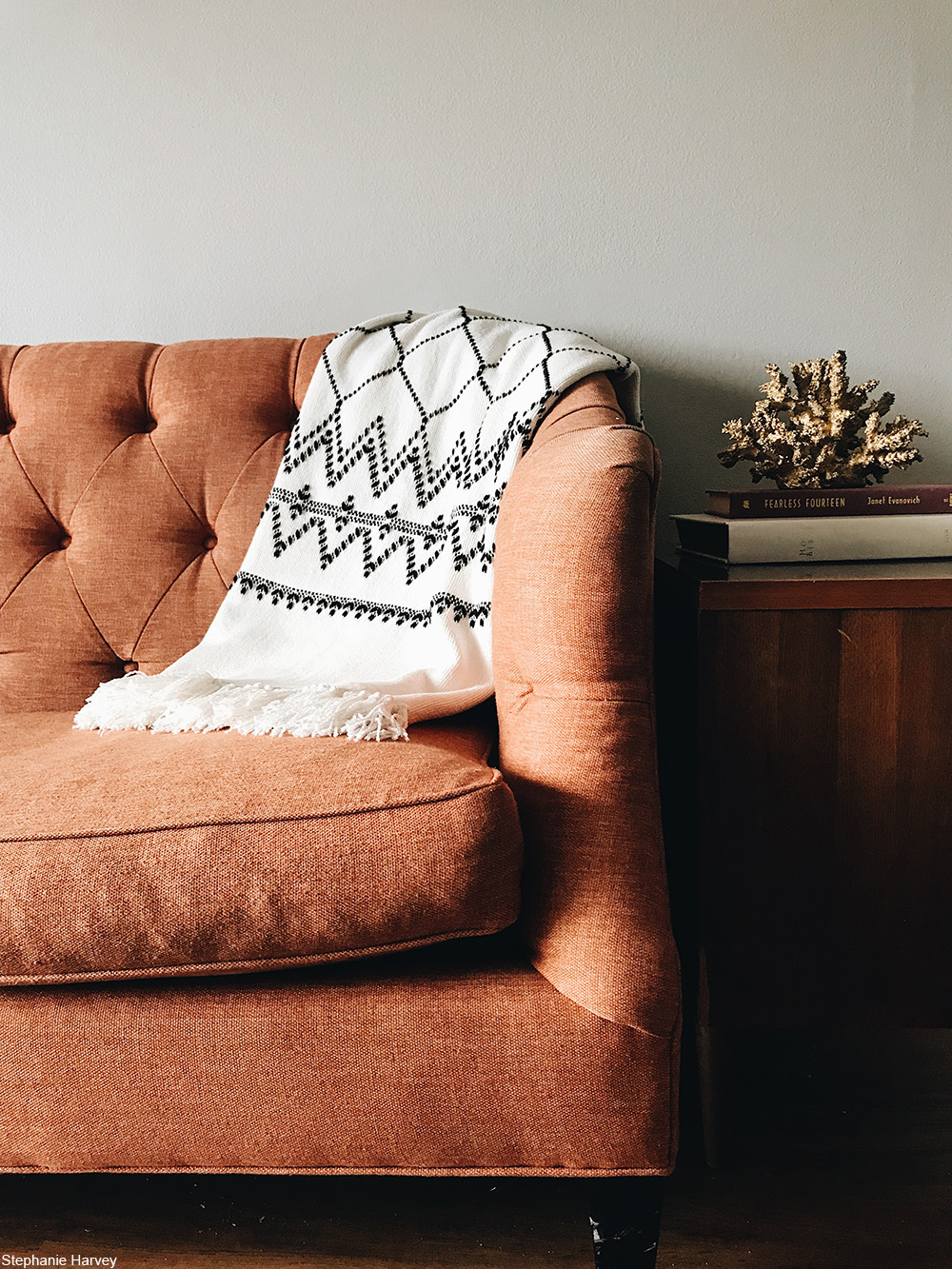 coral tufted sofa against a wall