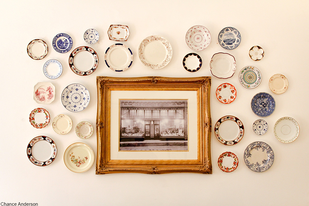 collection of plates hanging on a wall with a gold-framed photo