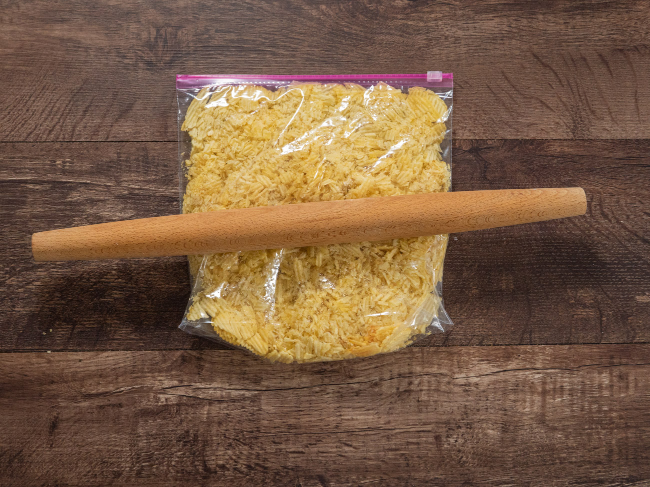 Grease a 9x9 pan. Crush the potato chips with a rolling pin and set aside.