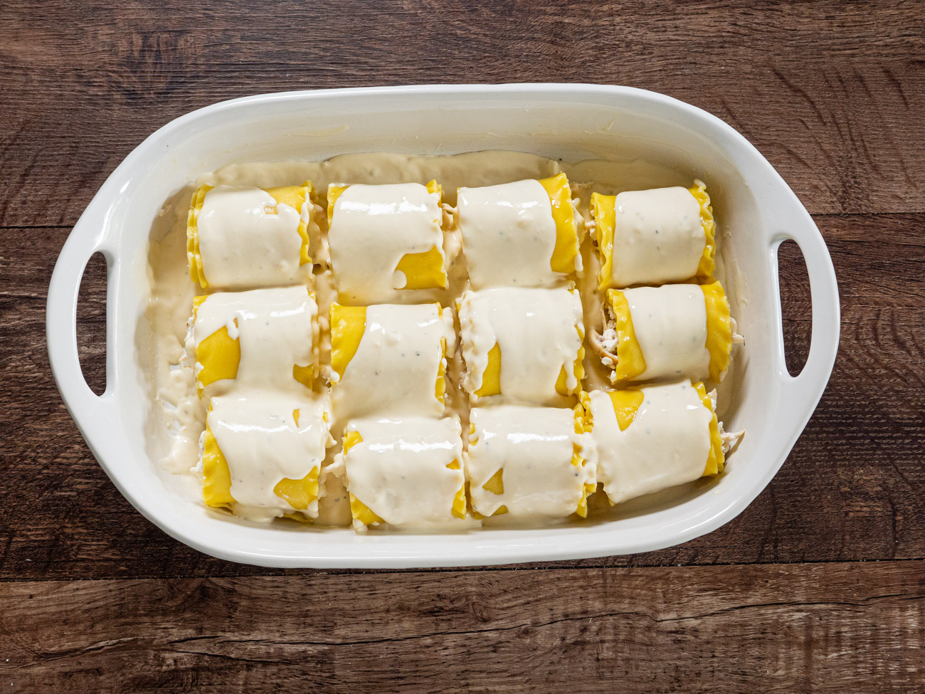 Place each lasagna roll up into the prepared casserole dish. Pour the remaining alfredo sauce over the lasagna roll-ups. Top with shredded mozzarella and parmesan cheese.