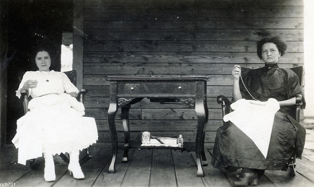 two women from around 1900 sewing on a front porch