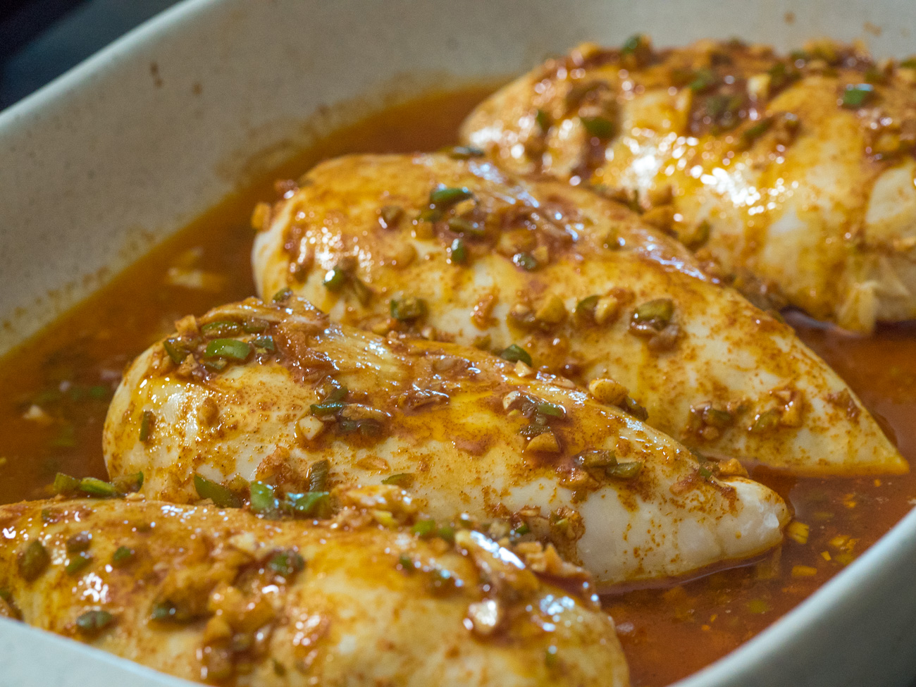 Remove chicken from pan and coat with piri piri sauce. Sauté for 2-3 minutes on each side for seared flavor.