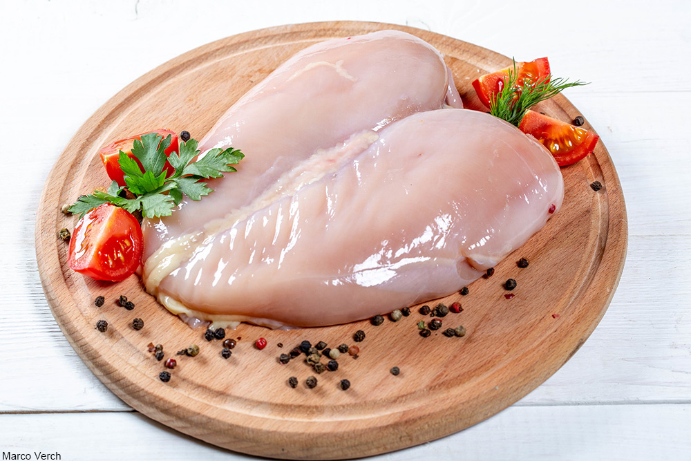 raw chicken breast surrounded by peppercorns
