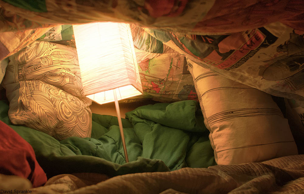 blanket fort with a lamp inside it