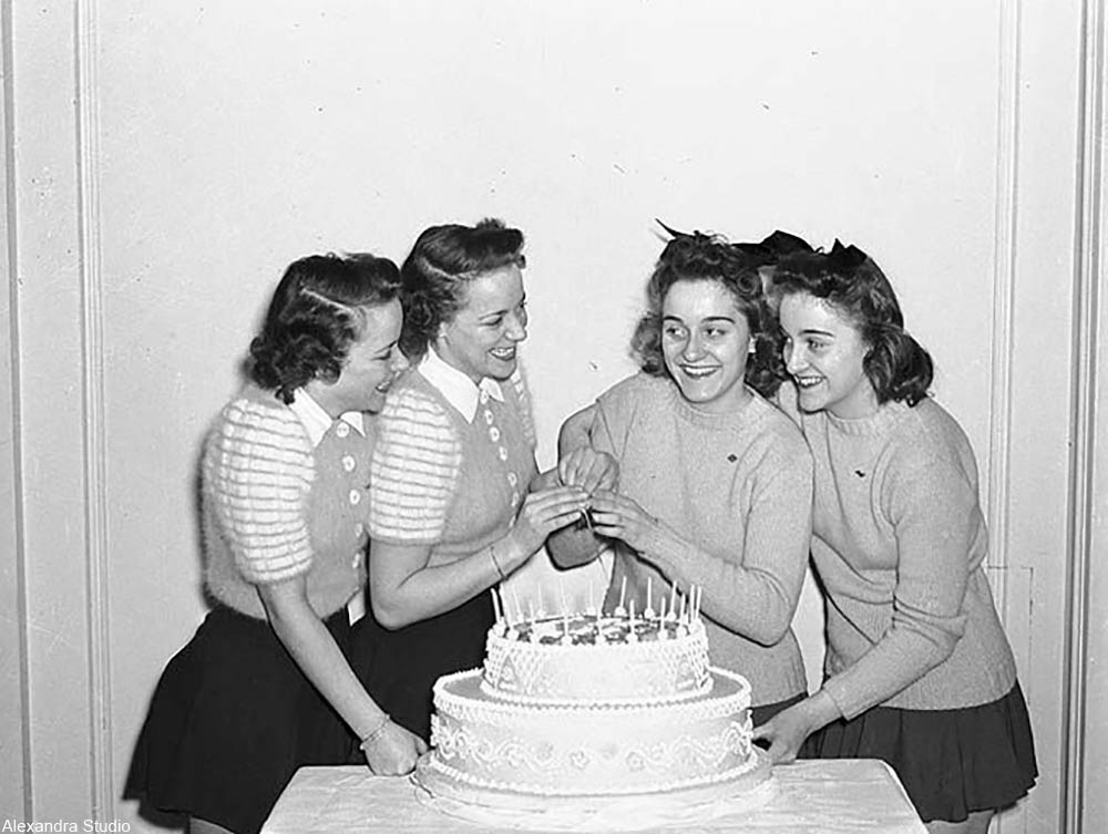 teenaged girls with a birthday cake in the 1950s