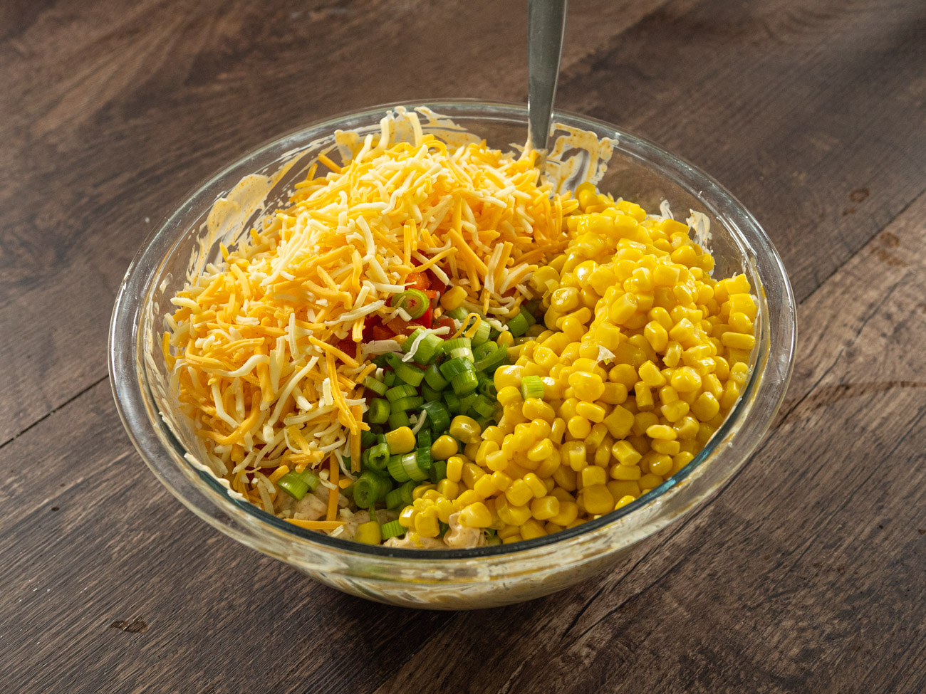 Add green onions, bell pepper, corn, and cheese. Toss again to mix and then allow to chill in the fridge for 1-2 hours before serving.