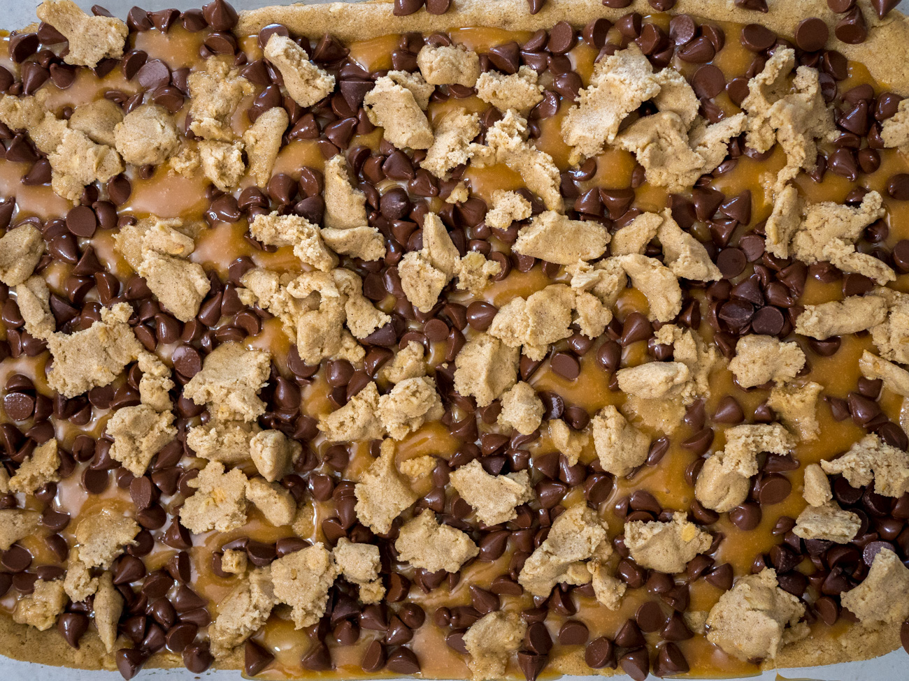 Crumble remaining cookie dough evenly over chocolate and caramel. Bake for another 15 minutes. Cool completely before cutting into bars. Serve and enjoy!