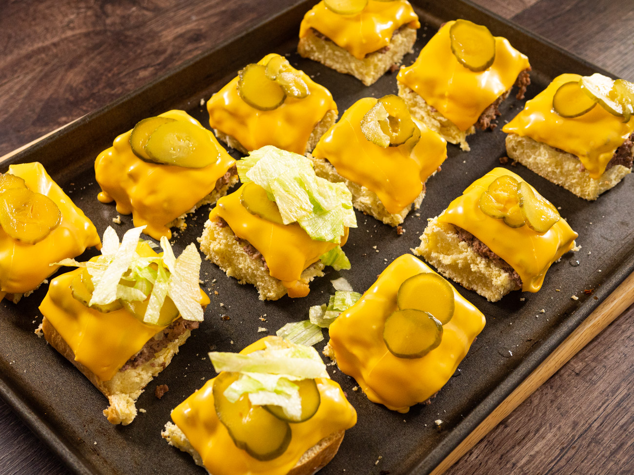 "Place cheese slices across the cooked mean and bake for another minute or two, until the cheese melts. When the cheese is melted, spread out pickles and lettuce on top and then place the ""lids"" on top."