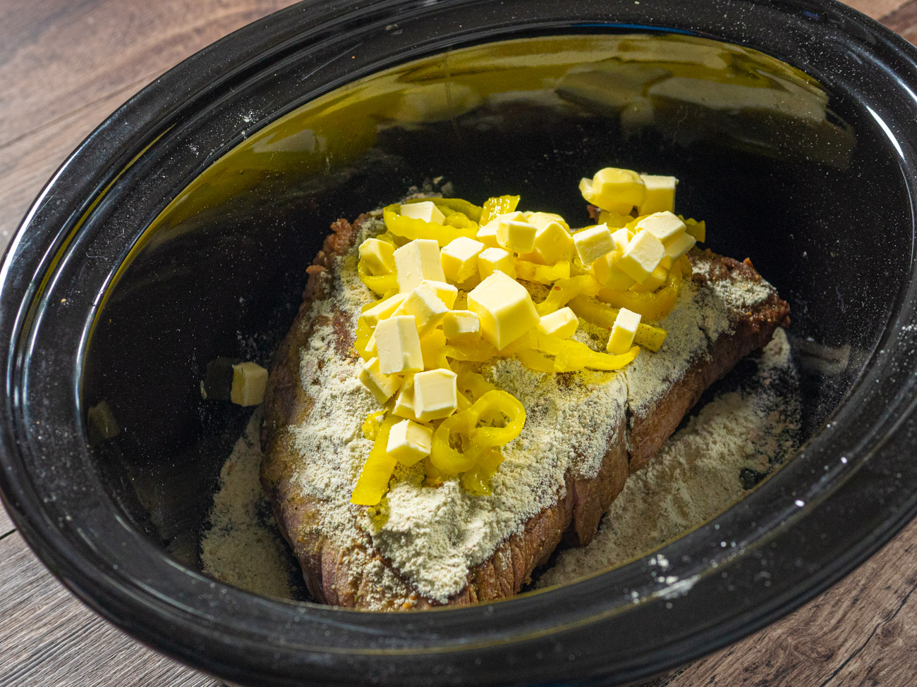 Place meat in bottom of slow cooker and pour soy sauce over meat. Sprinkle dry seasoning mixture on top. Add pepperoncini peppers and butter cubes on top of meat.