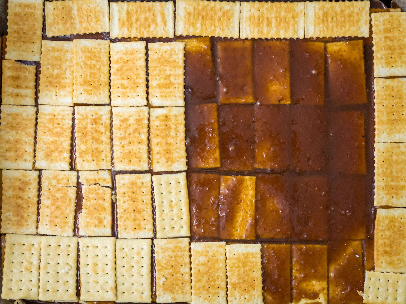 Pour the rest of the caramel over the second layer of crackers, and then add a final layer of crackers. Refrigerate while working on the chocolate topping.