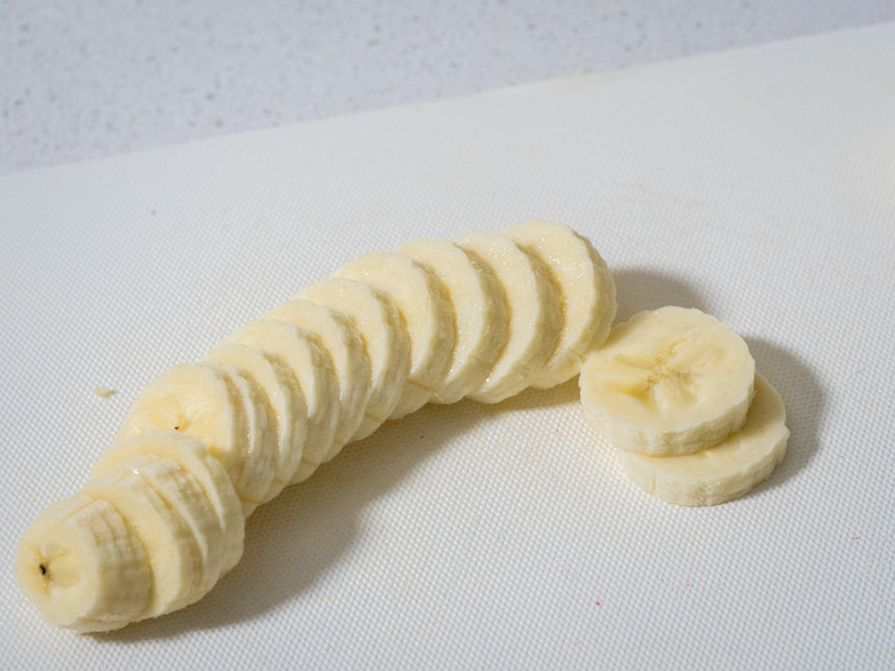 Slice bananas and place half a sliced banana around the rim of each bowl or cup.