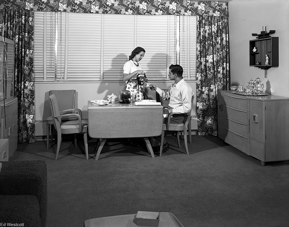 mid-century housewife serving breakfast to her husband