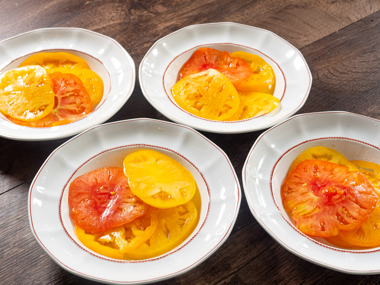 """Slice tomatoes into 1/3"""" slices. Divide them equally among four plates. Lay out tomatoes slightly overlapping each other- as if a set of dominoes has just been toppled."""