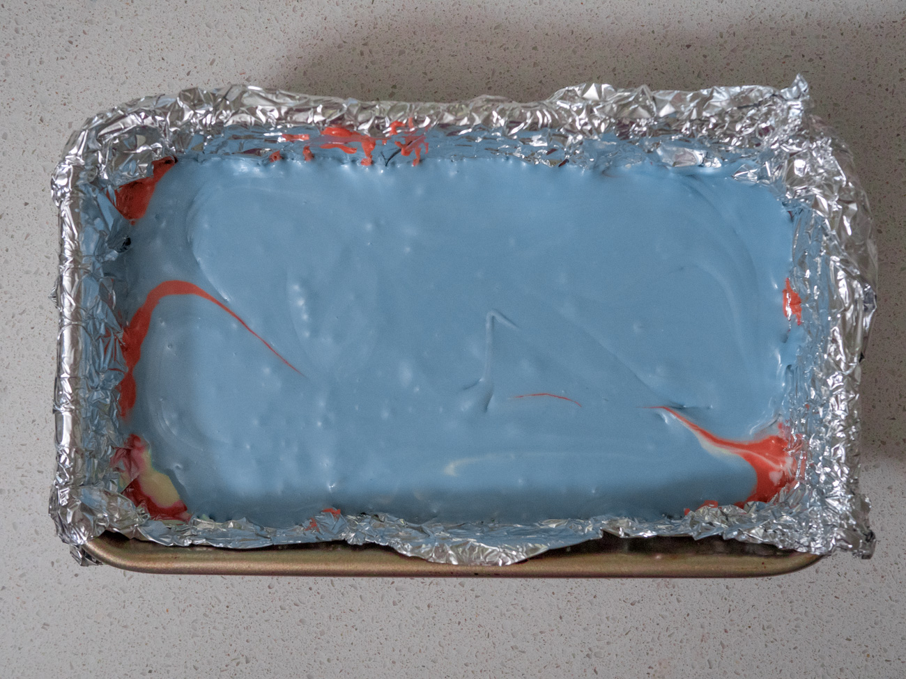 Pour the fudge into the loaf pan in layers in the order of red, white, and finally blue. Smooth each layer with the back of a clean spoon.