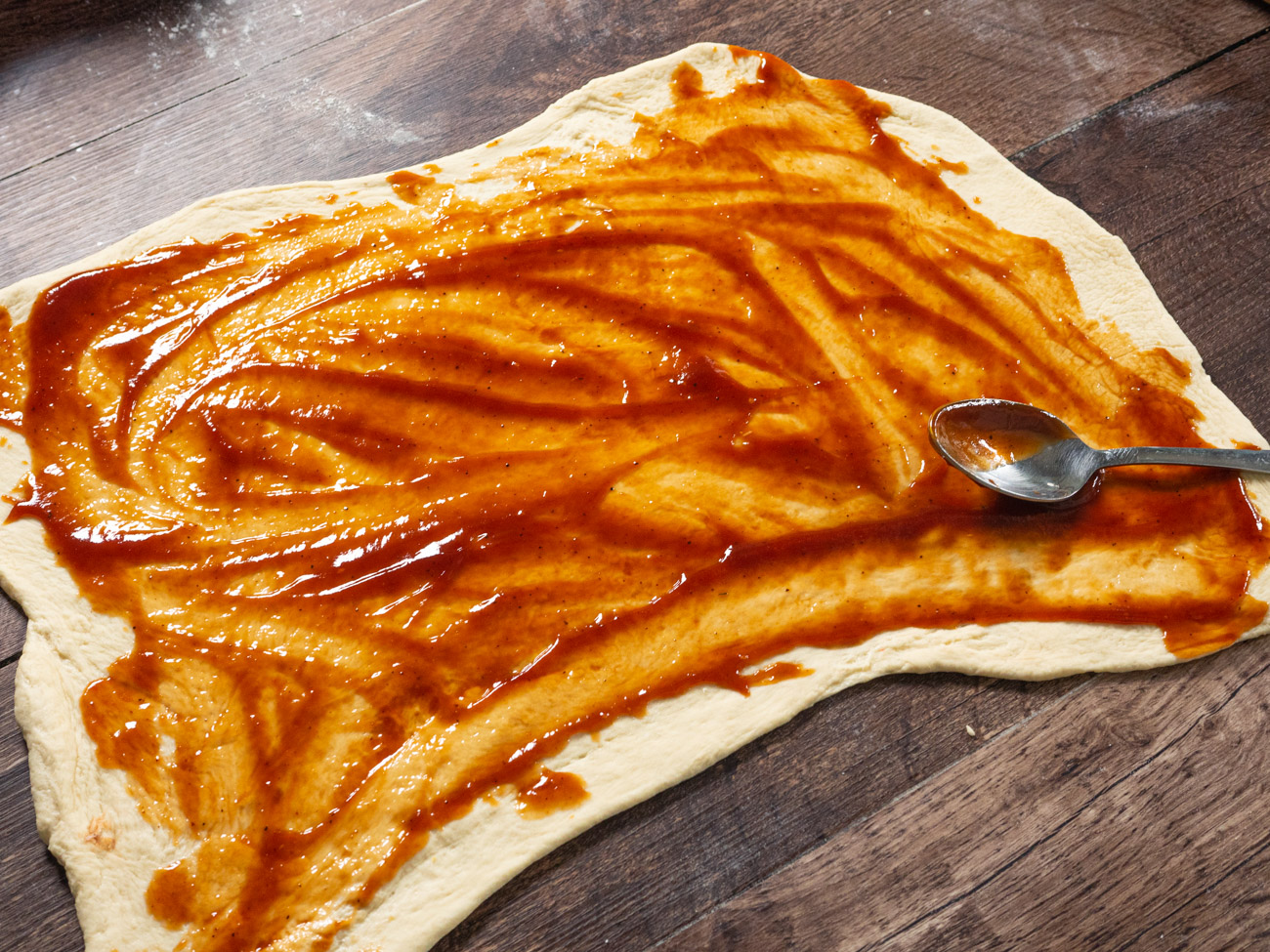 Spread BBQ sauce over the surface of the dough leaving a 1/2-inch border all around the edges.