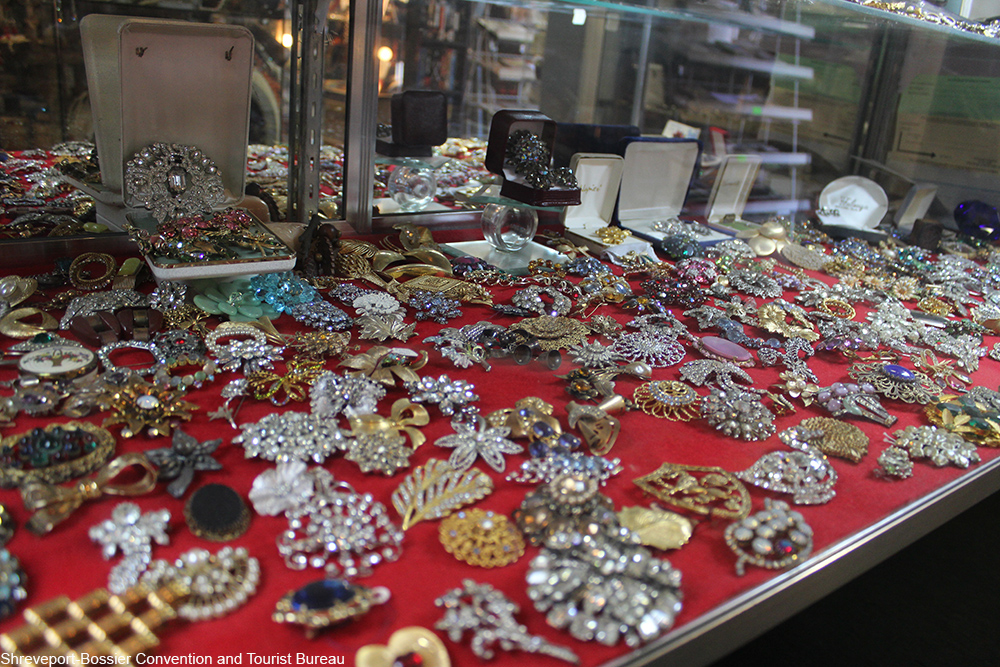 a selection of vintage brooches inside a glass case