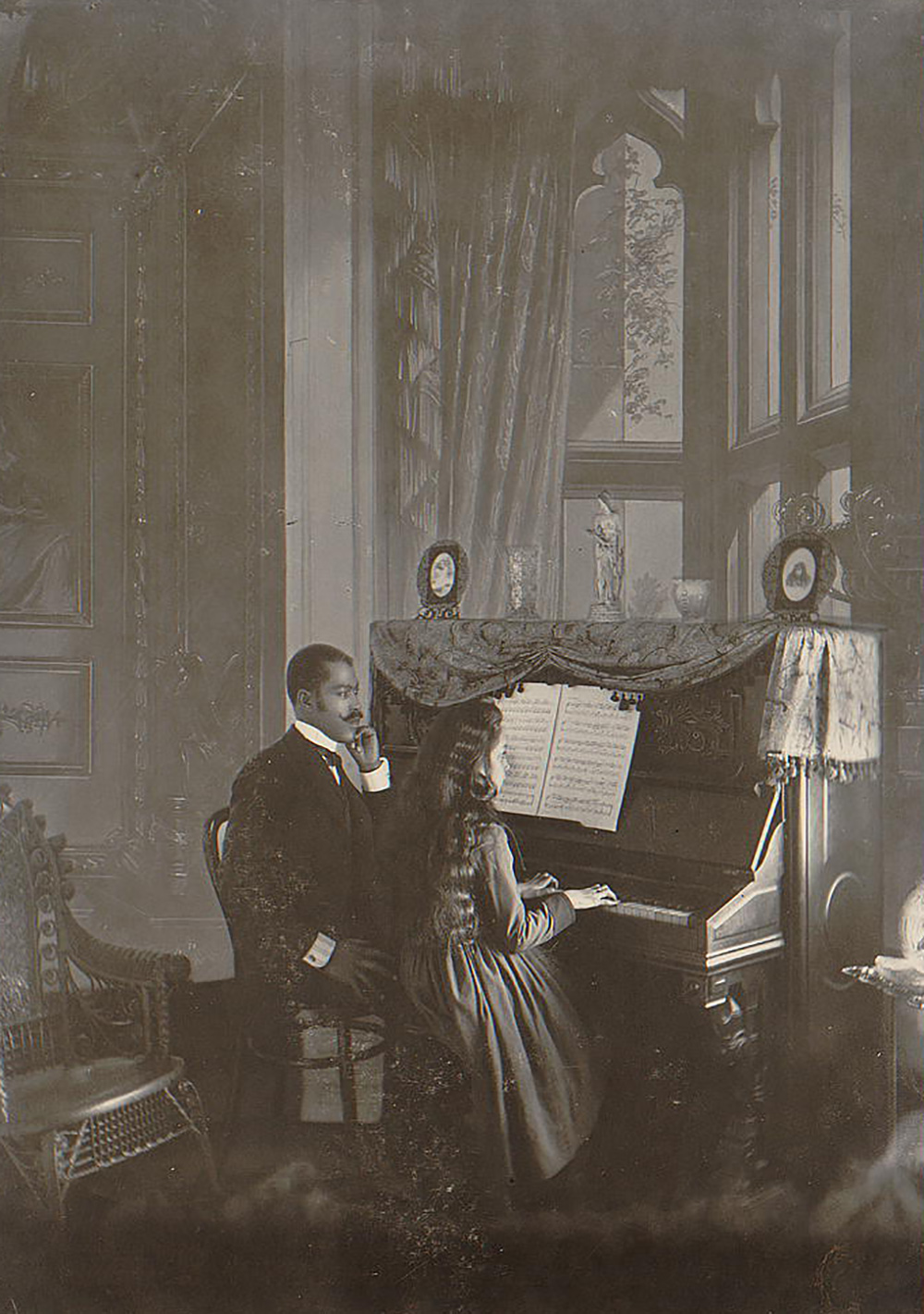African American man giving piano lessons in the 1890s