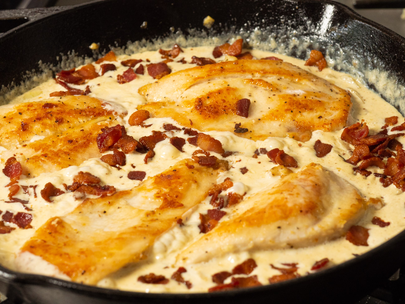 Add the chicken back into the pan and coat with sauce. Top each serving with the crispy bacon pieces. Serve over pasta.
