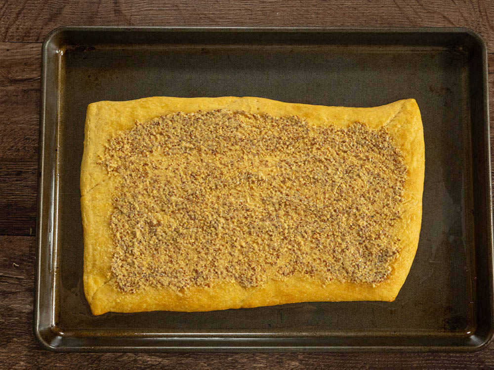 To build the squares, spread an even layer of mustard onto the baked bottom layer of crescent roll, leaving a half-inch border clear on all edges.