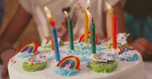 child's birthday cake with rainbows and candles