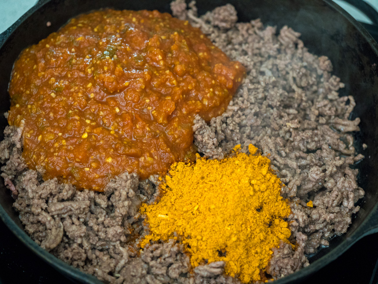 Brown hamburger in a large skillet over medium heat, then mix in salsa and taco seasoning.