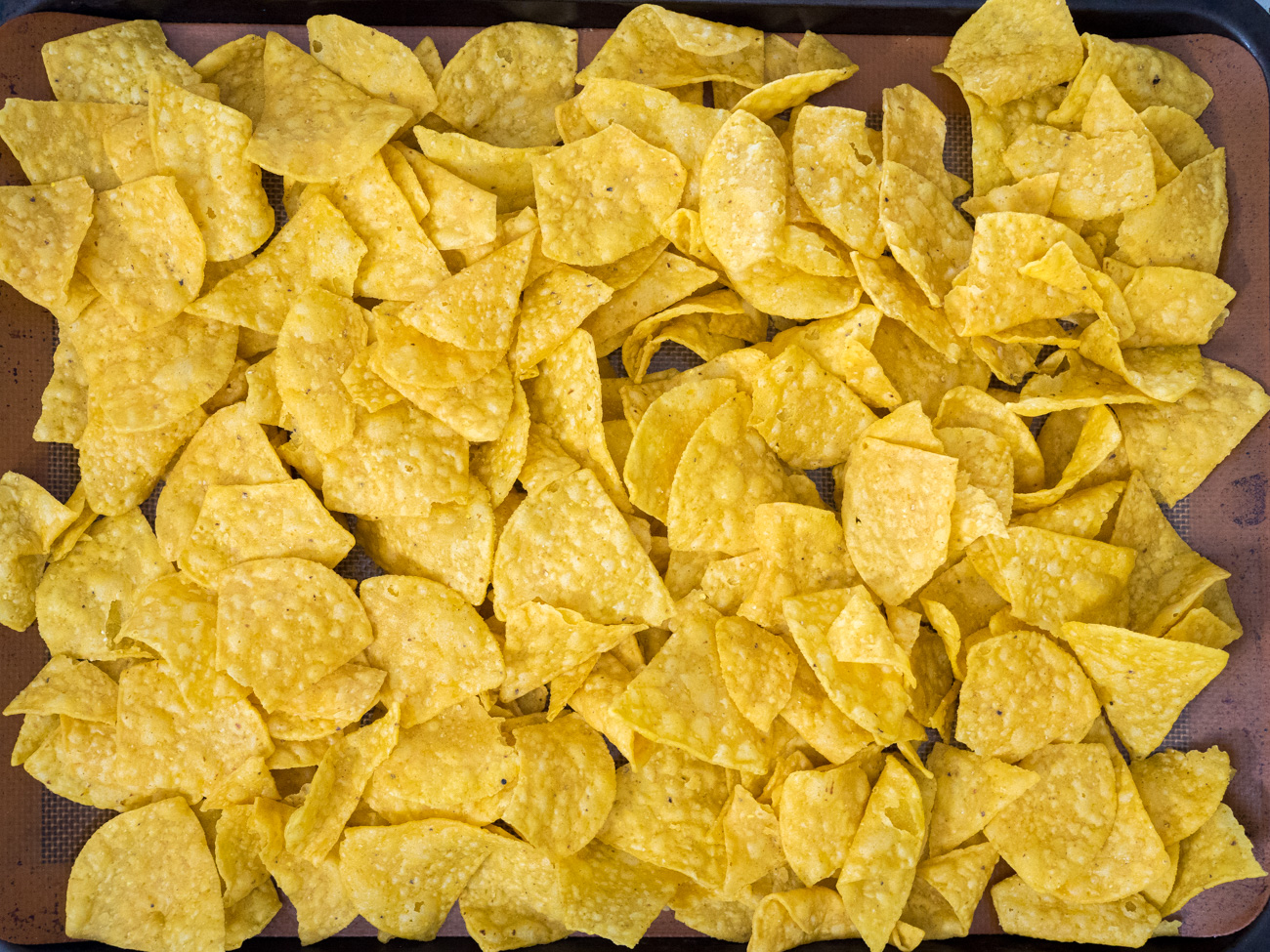 Spread out tortilla chips in a single layer on the prepared baking sheet.