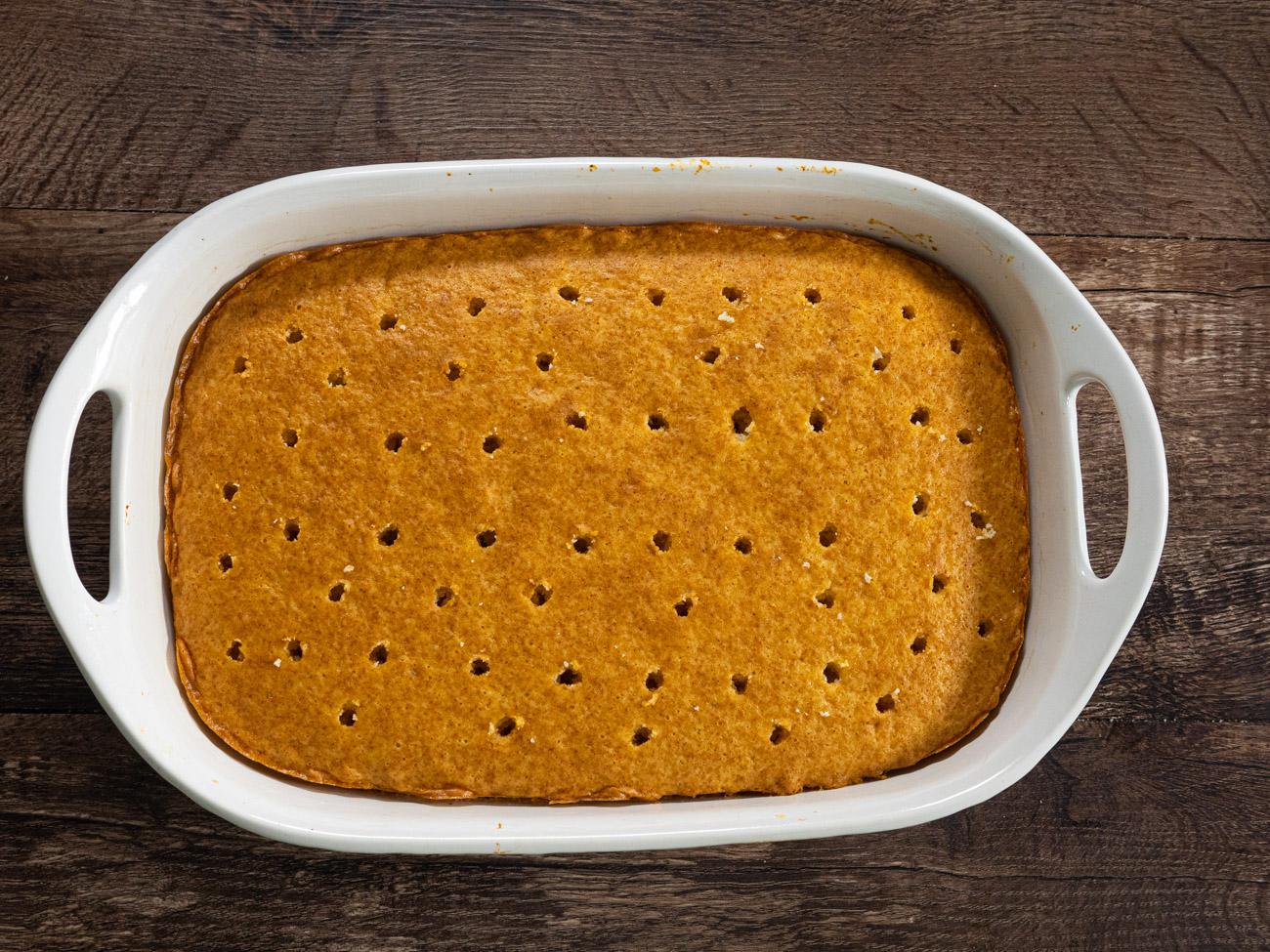 Remove the cake from the oven and allow to cool. Once cooled, use the handle of a wooden spoon to poke holes in the cake every inch or so, only pressing down halfway.