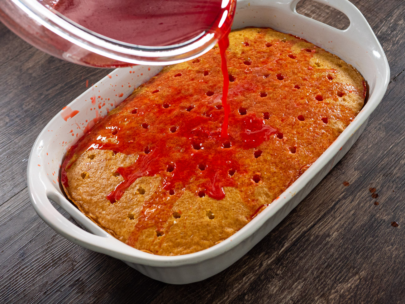 Combine raspberry gelatin and hot water until dissolved. Pour evenly over the cake, filling in the holes.