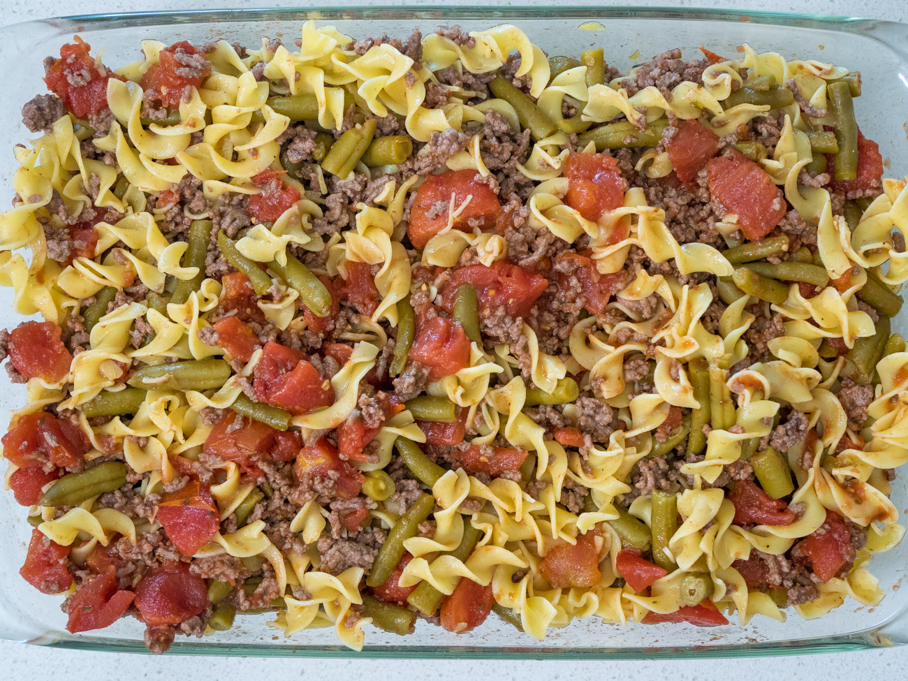 Preheat oven to 350˚. Add tomatoes and drained green beans to beef and stir. In a 9x13 casserole dish combine beef mixture with the egg noodles.