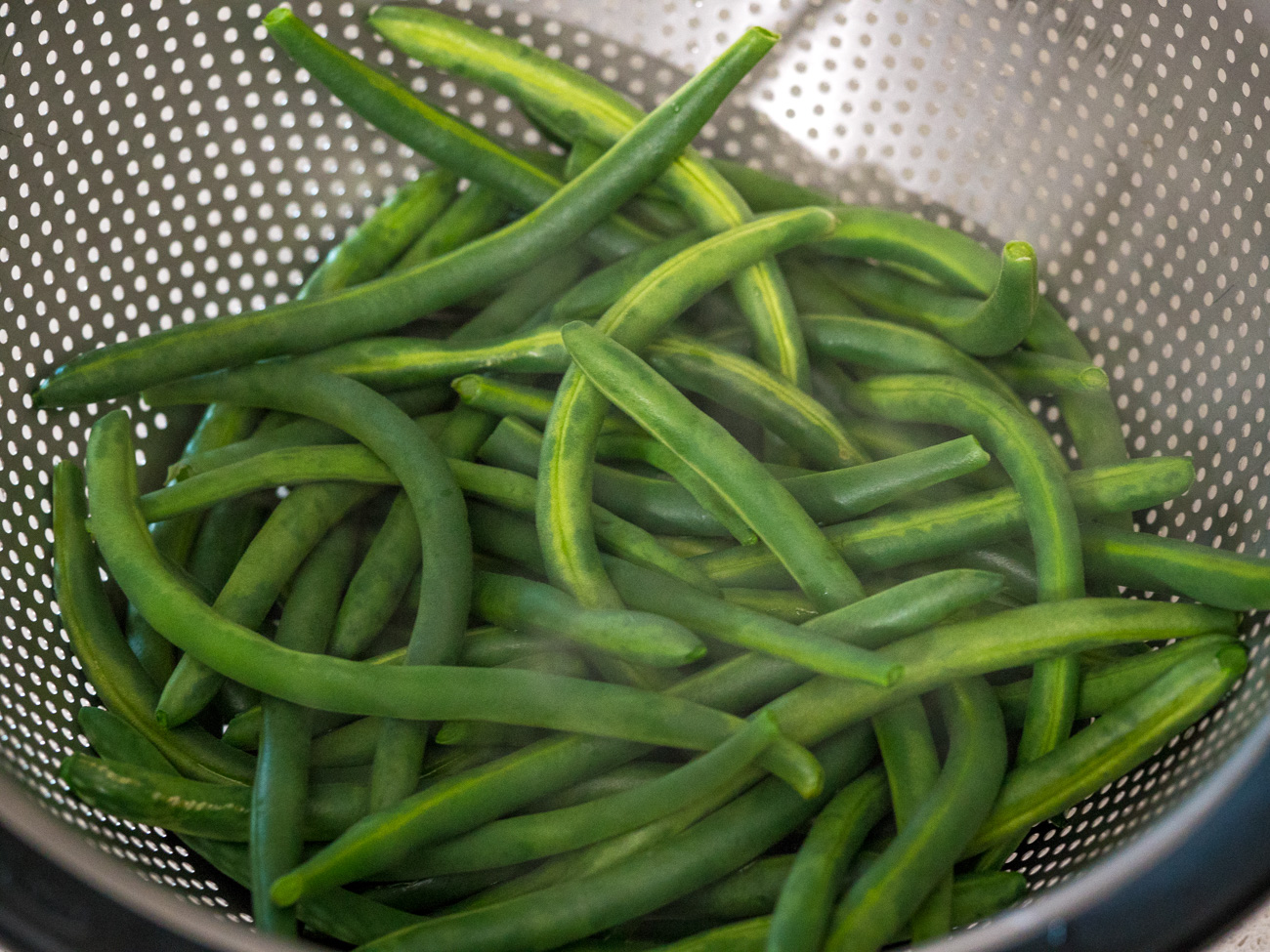 Fill a large pan with 1 inch of water and bring to a boil. Add green beans and blanch for 3 minutes. While the green beans cook, fill a large bowl with ice water and set aside.