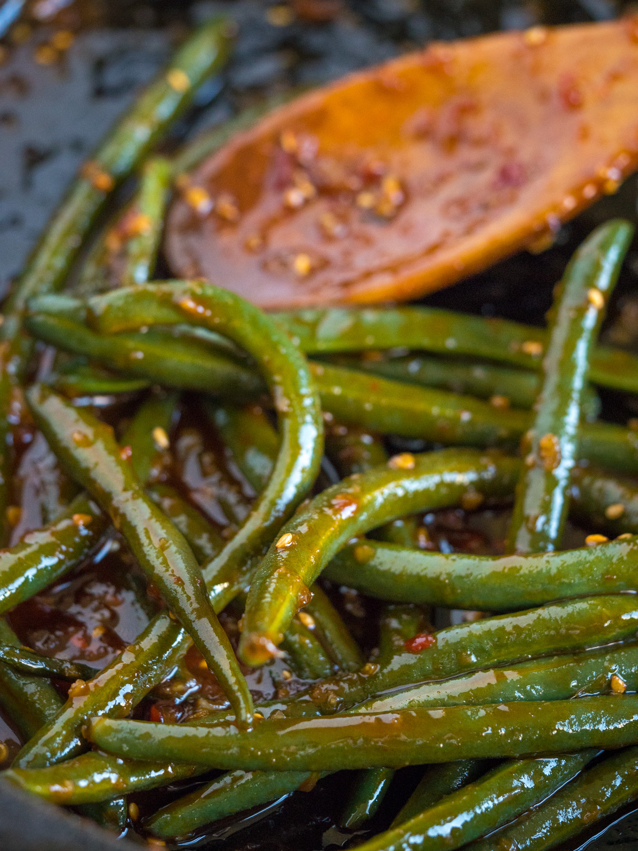 Add Sriracha mixture to the pan and simmer uncovered for a few minutes. Once the green beans are tender, toss with sesame seeds and serve up hot!
